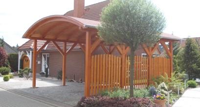 Carport mit Tonnendach und Holzzaun