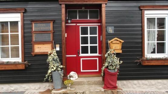 Rote Haustür eines Holzhauses